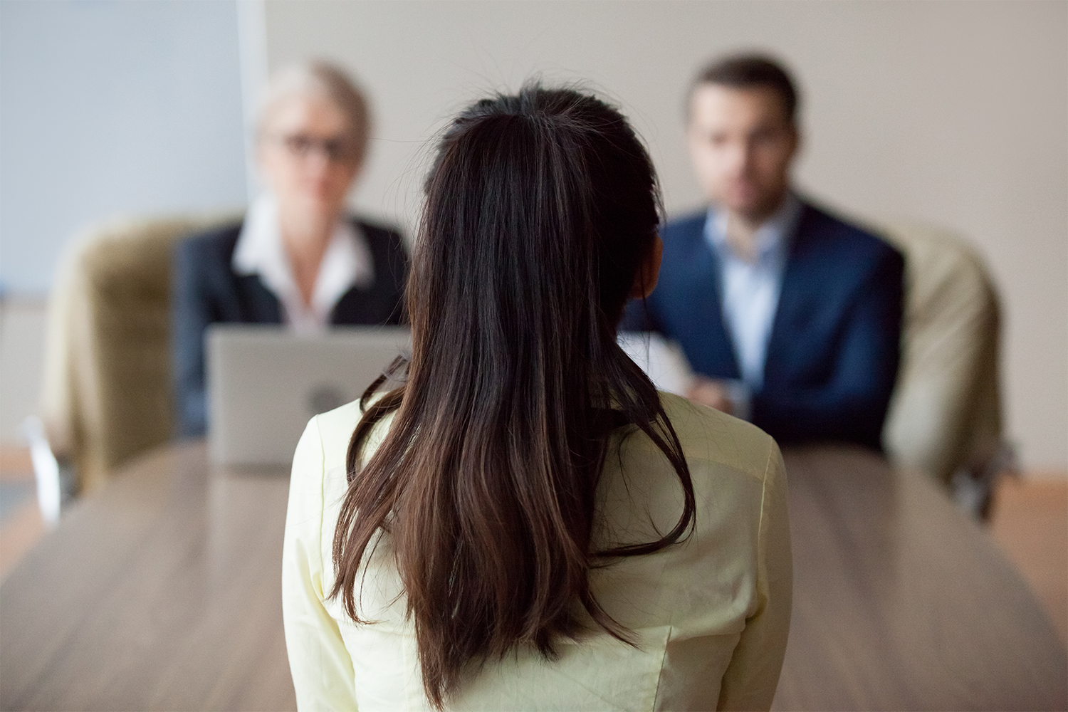 Businesswoman and businessman HR manager interviewing woman.