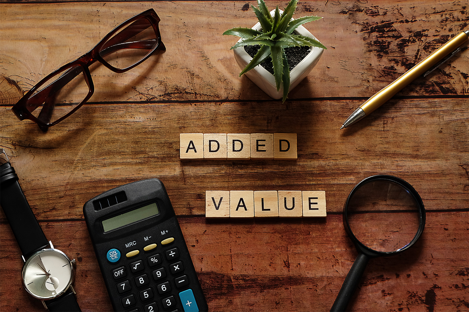 Top view wood text Added value with brown glasses,calculator,gold pen,black watch,magnifying glass and white pot plant.